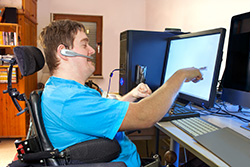 Image of a man in a wheelchair working on a computer
