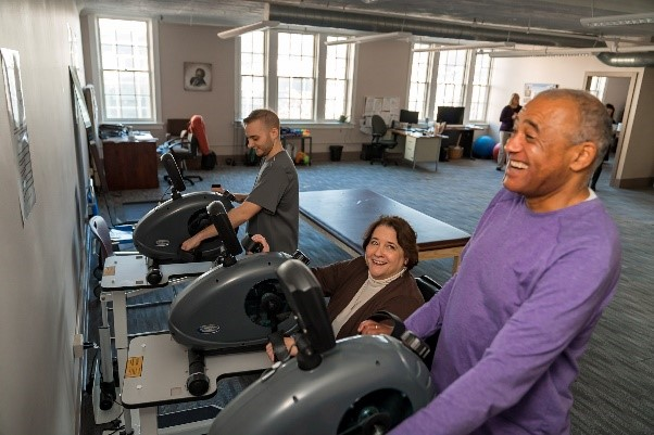 Image of three individuals of varying abilities exercising and smiling
