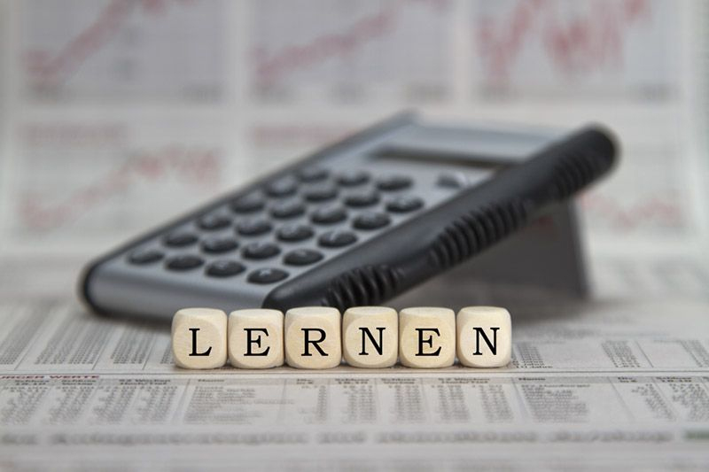 A calculator sitting on the newspaper financial section with letter-cubes spelling out 'LERNEN'